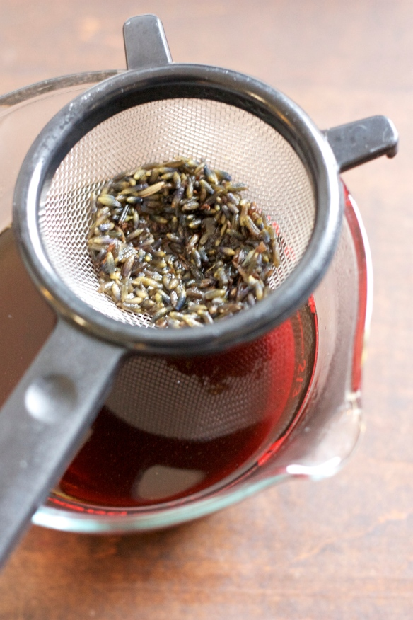 lavender buds in strainer over contained liquid